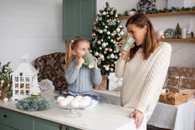 Girl and mother drinking tea from cup in christmas kitchen at home.