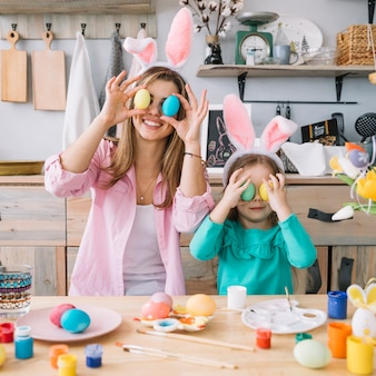 Girl and mother holding easter eggs at eyes