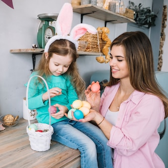 Girl and mother sitting with easter eggs near basket