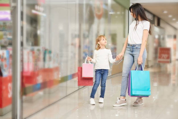Girl and mother standing near shop window of shopping mall.