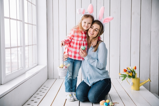 Girl and mother standing with basket of easter eggs