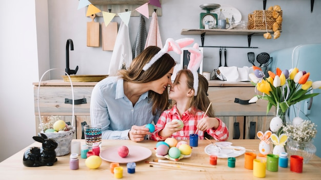 Girl and mother touching noses while painting eggs for easter
