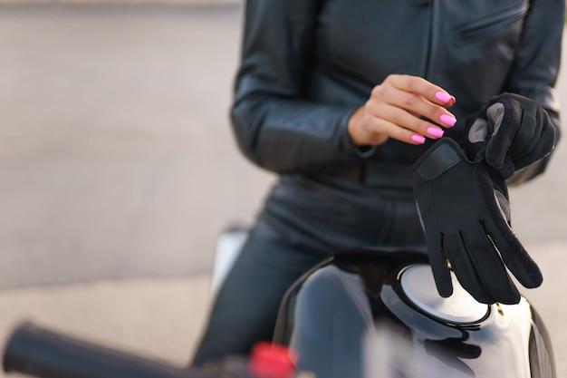 Девушка-мотоциклист в перчатках