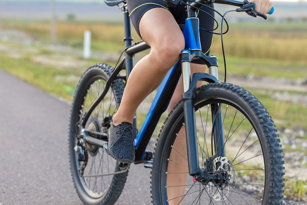 Girl on a mountain bike on offroad beautiful portrait of a cyclist girl rides a modern carbon  bike