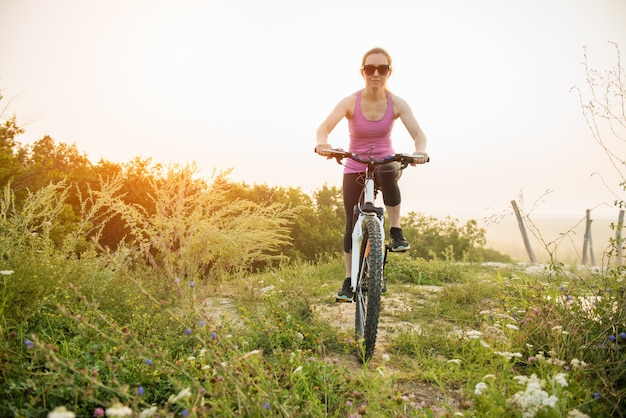 Girl on mountain bike rides on the trail on a beautiful sunrise