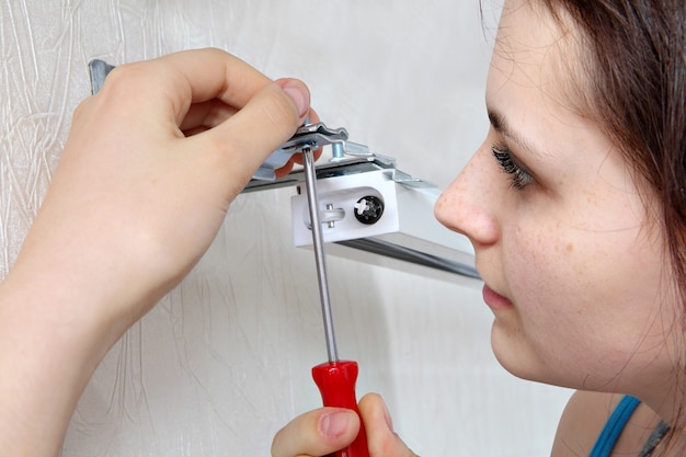 Girl mounts vertical blinds on the wall,  tighten screw red screwdriver