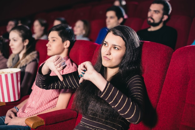 Girl in a movie theater in the session of the film that she does not like