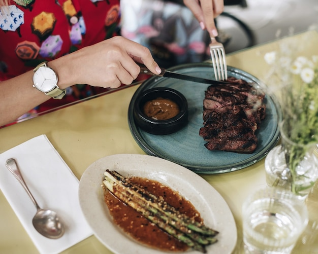 A girl in a multi-colored dress sieves a meat steak with a knife.