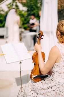 女の子のミュージシャンが譜面台の近くに座って、結婚式の背面図の間にバイオリンを保持します