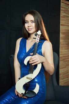 Девушка-музыкант со скрипкой в руках в сценической одежде. женщина играет на современной скрипке