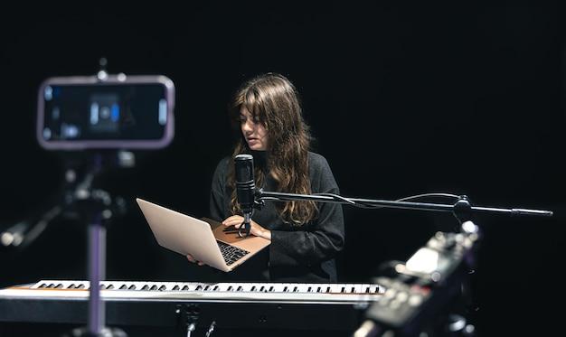 ノートパソコンを持った女の子のミュージシャン、三脚の上に立ってスマートフォンでビデオを録画し、プロのマイク、ブロガー、またはスタジオで音楽教師の撮影コースを使用して、ピアノに座っています。