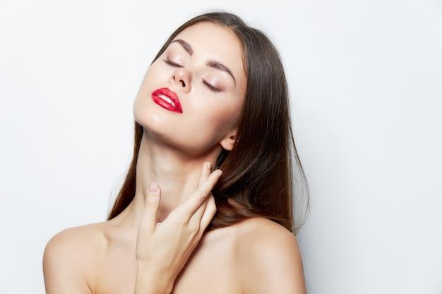 Девушка обнаженные плечи закрытые глаза красные губы очарование ярким макияжем изолированный фон
