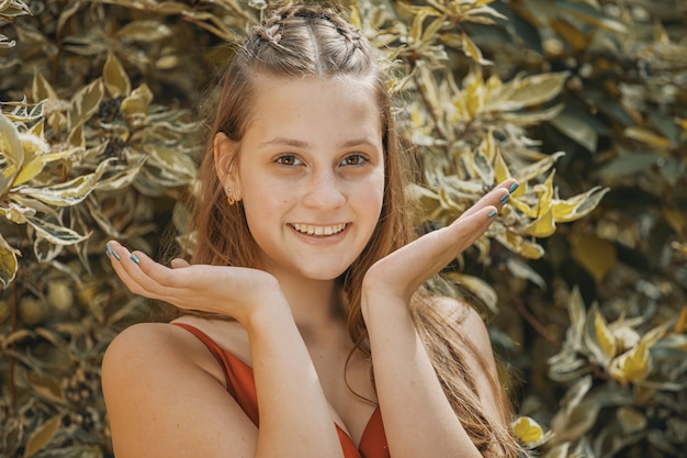 Girl in nature holds palms to her face and smiles