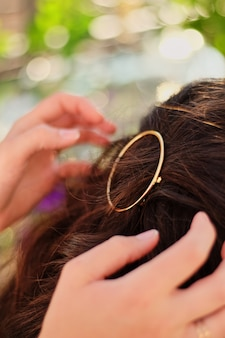 Girl on nature, straightens the hair pin