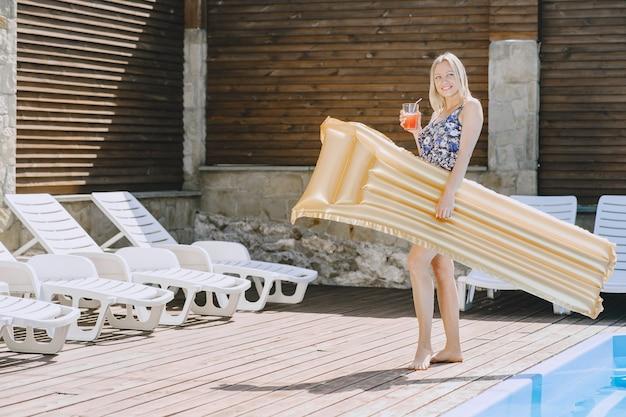 プールの近くの女の子。スタイリッシュな水着の女性。夏休みの女性
