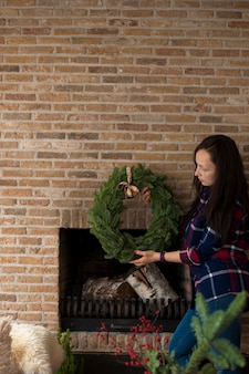 Girl near the fireplace with a brick wall and a wreath of christmas tree