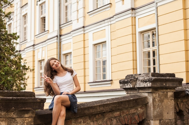 Girl near the hight school building. education concept, end of school. summer holidays