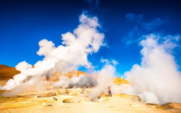 Girl near huge steaming geysers in sunshine bolivia