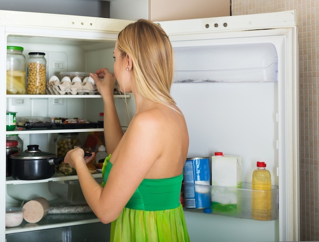 Girl near opened refrigerator in kitchen