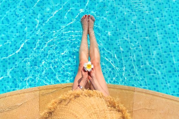 Девушка возле бассейна с цветком