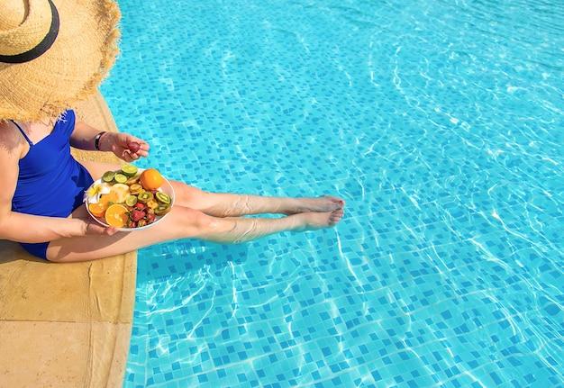 果物とプールの近くの女の子