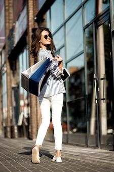 A girl near the wall of a shopping center.