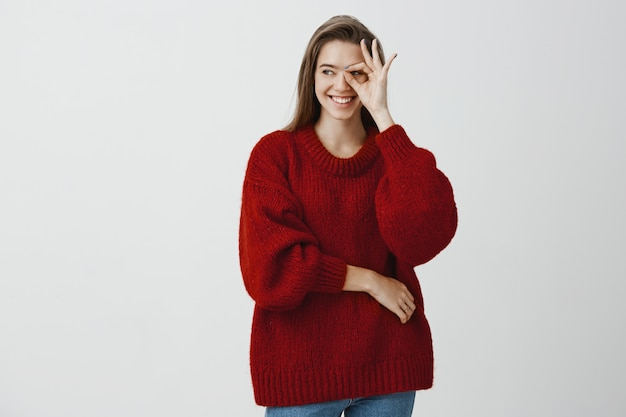 Girl never stops looking after her boyfriend. confident joyful caucasian woman in loose red sweater, showing okay or great sign over eye and looking aside with happy smile