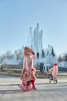 Girl new fashion vogue creative clothes posing outdoors, pink dress and hat, ethnic clothing