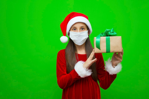 Girl in a new years cap in medical mask holds gift for christmas in hands place for advertising