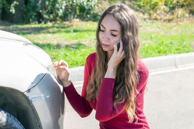 女の子は車のバンパーに新鮮な傷があることに気づき、動揺しています。そして彼女は警察と保険に電話します