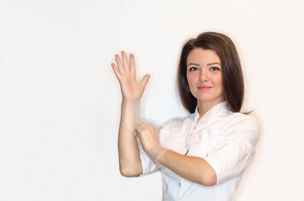 Девушка медсестра, женщина, женщина-врач в белом халате надевает на руки стерильные белые латексные перчатки для процедуры, операции. здравоохранение.