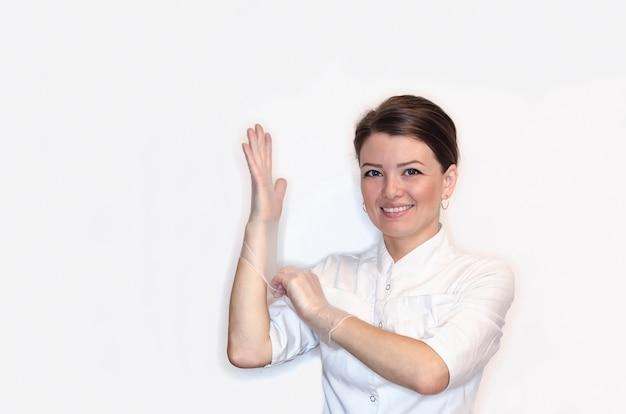 Девушка медсестра, женщина, женщина-врач с улыбкой в белом халате, надевает на руки стерильные латексные перчатки для процедуры, операции. здравоохранение.