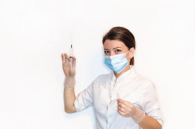 Девушка-медсестра, молодая женщина, женщина-врач в белом халате, стерильные белые латексные перчатки, маска с шприцем для инъекций, вакцинация, обезболивание.