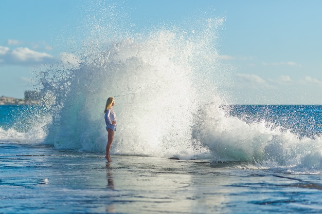 Girl  on the ocean against the big  waves, canary islands, tenerife