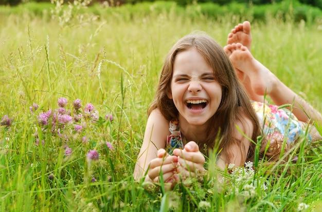 10歳の女の子が花の間の草の上に横たわって笑う