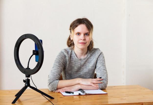 Девушка 16 лет записывает видео на смартфон и освещает себя кольцевой лампой за столом в светлой комнате