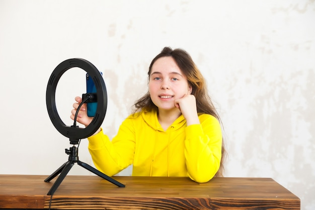 スマートフォンでビデオを録画し、ライトルームのテーブルでリングランプで自分自身を照らす16歳の少女