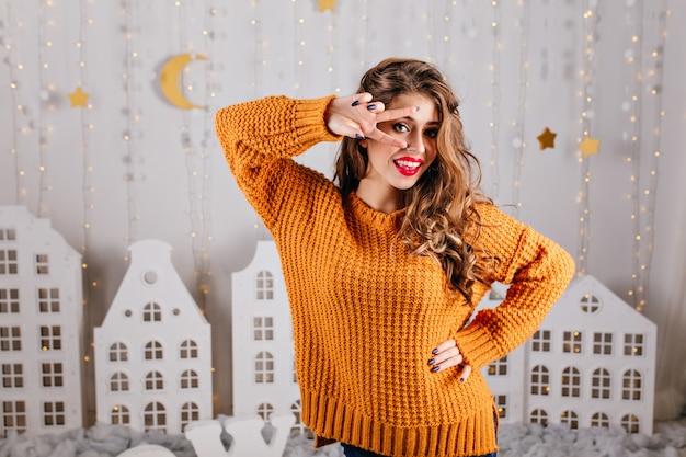 Девушка 25 лет с вьющимися волосами и голубыми глазами, позирует, показывая знак мира. портрет привлекательной славянской натурщицы в великолепном интерьере