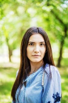 緑の葉を背景に若いタタール人の都市公園夏の肖像画でアジアの外観の女の子
