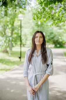 都市公園の散歩にアジアの外観の女の子。若いタタール人の夏の肖像画