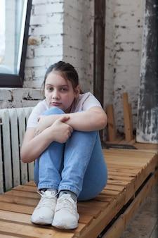 彼女の膝を抱き締めて、窓の近くで悲しい十代前の年齢の女の子