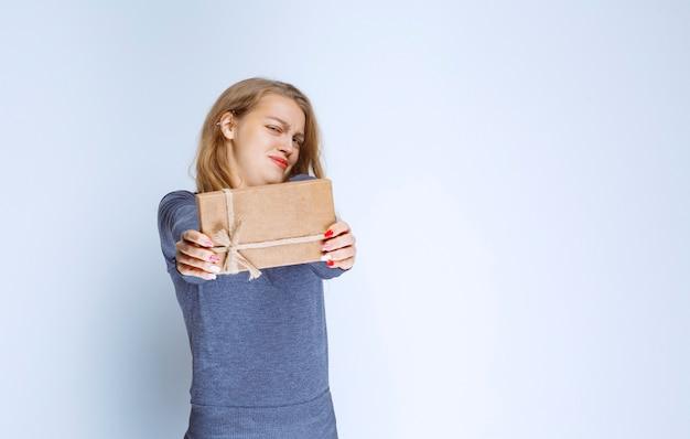 Девушка предлагает картонную подарочную коробку с сердитым лицом.