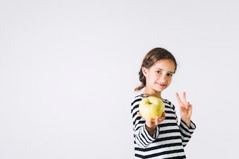 Girl offering apple and gesturing peace