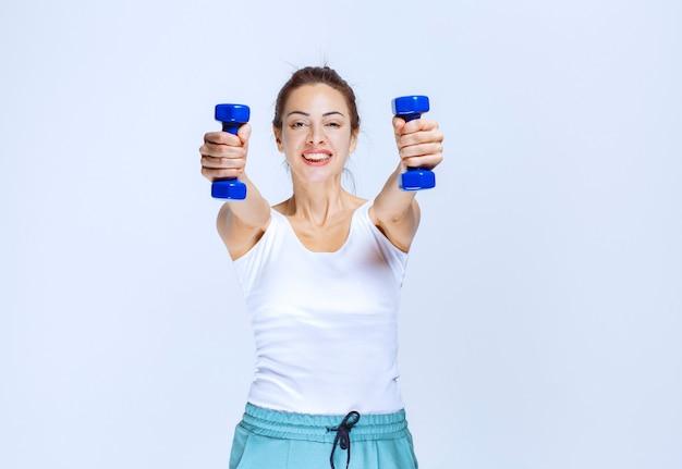 別のトレーナーに彼女の青いダンベルを提供している女の子。