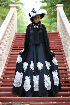 Girl in old retro dress on stairs outdoor