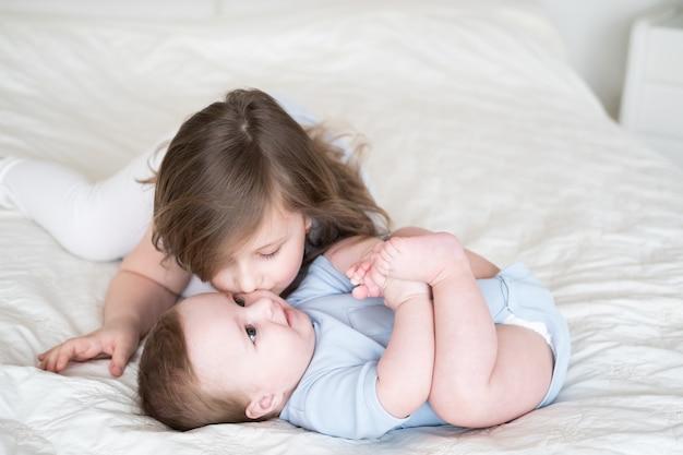 Девушка старшая сестра целует своего маленького брата мальчика на кровати у себя дома