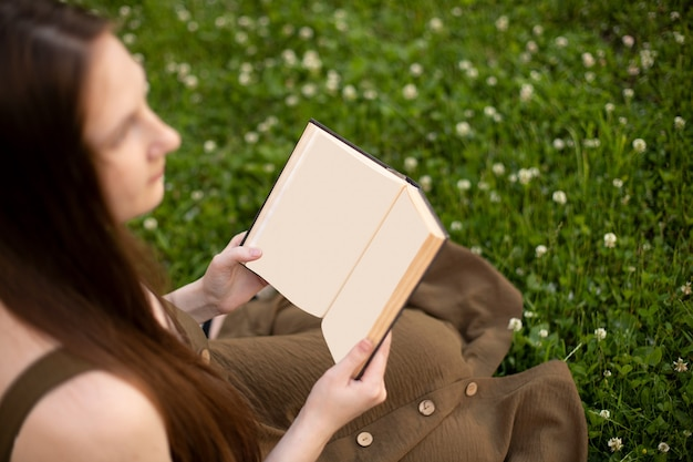 Girl in an olive dress holding a book with a blank page in her hands sitting on the green grass