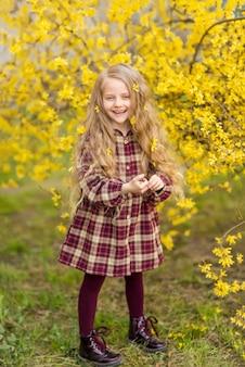 黄色い花を背景に女の子。咲く春の庭の子供