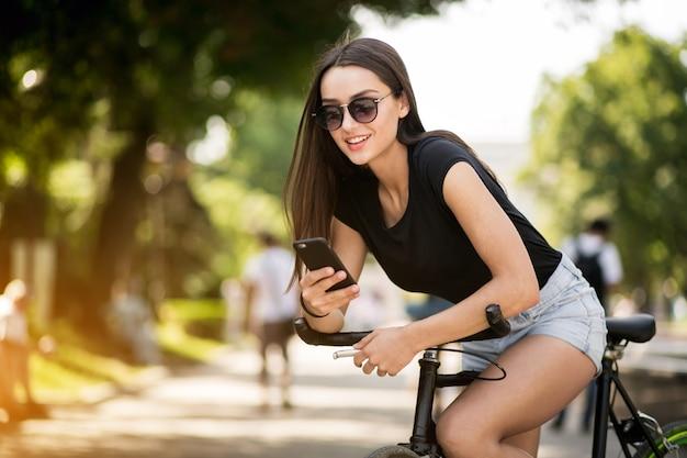 電話で自転車に乗る少女