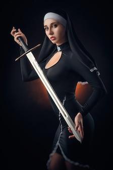 Девушка на черном фоне в платье монахини позирует с ружьем, прицеливание, стрельба